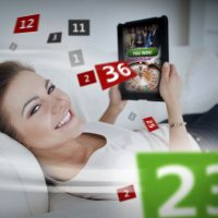 Woman lying on couch and gambling on tablet with holographic numbers around her